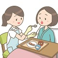 ベッドで食事介助をする女性
